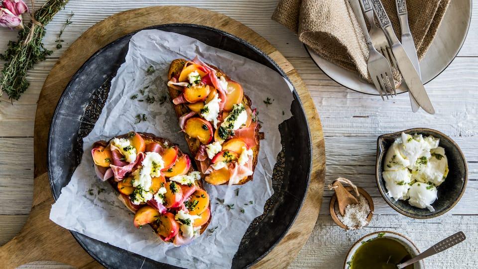 Fruchtige Crostini mit Plattpfirsichen und Büffelmozzarella: Eine sommerliche Vorspeise für laue Grillabende.