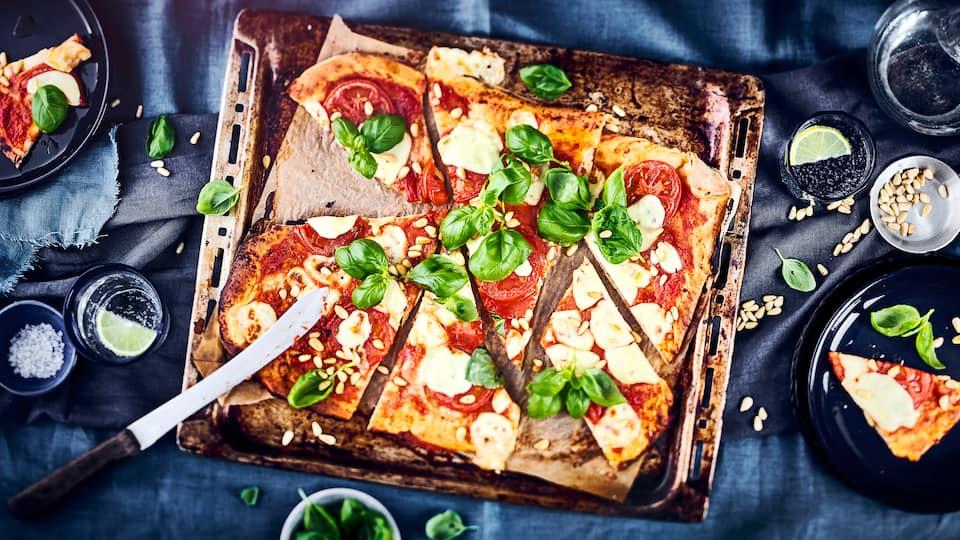 Pizza Caprese, mit selbst gebackenen Pizzateig, frischen Tomaten, Mozzarella und Pinienkernen. Perfekt für einen lauen Sommerabend mit Freunden mit einem feinem Rotwein.