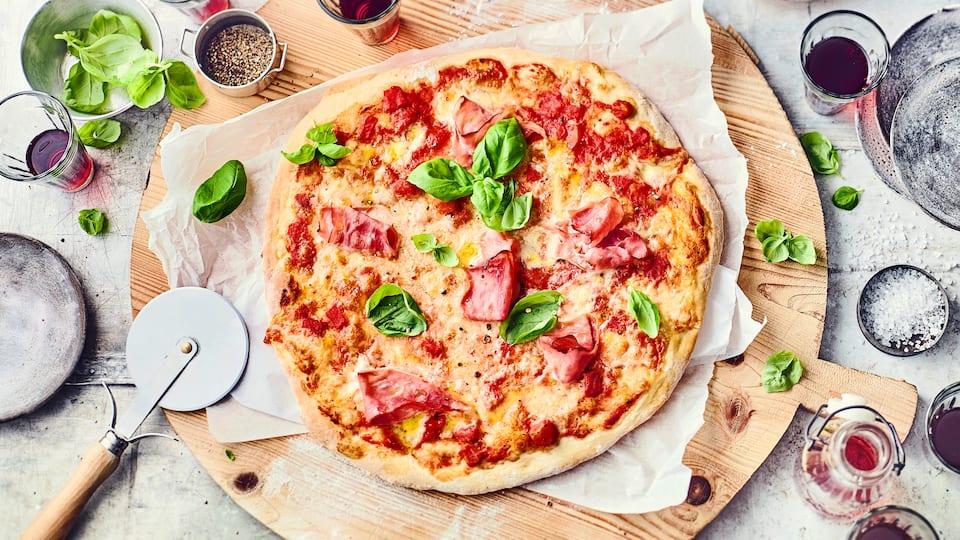 Sicherlich eine Lieblingspizzasorte von Vielen: Pizza Prosciutto mit Tomaten, Prosciutto, Mozzarella und frischem Basilikum.