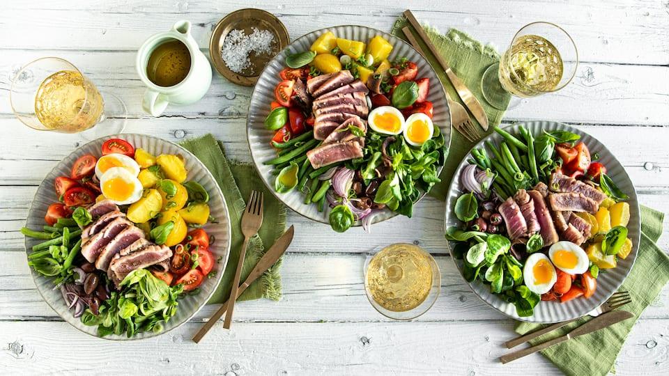 Es gibt den Nizza-Salat in mehreren Varianten, wir servieren den Klassikern mit Kartoffelsalat, Eiern, Bohnen, Tomaten, Sardellen und frischem Thunfischfilet.