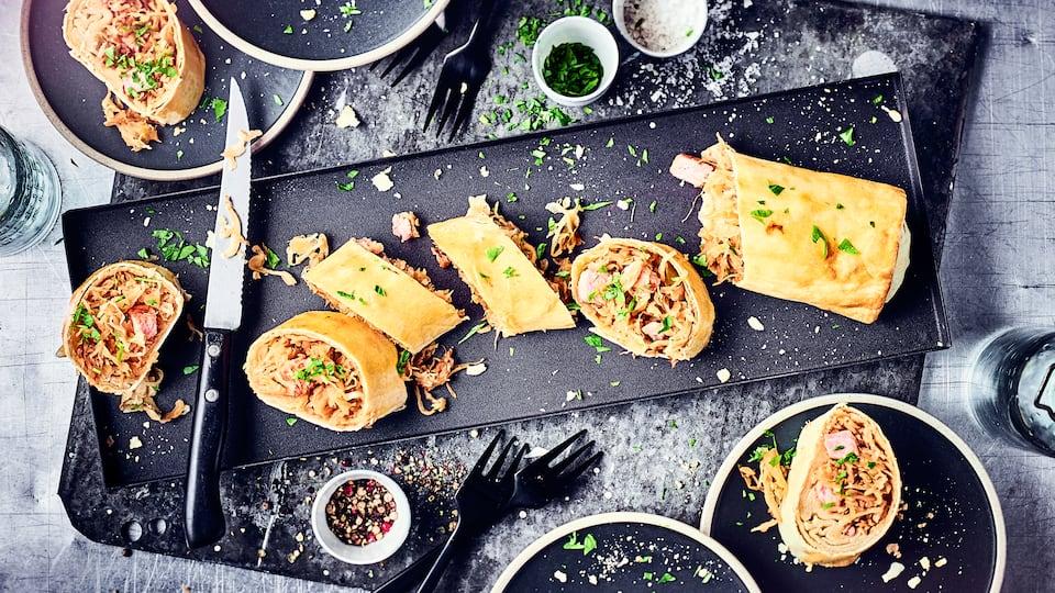 Unser Tipp für ein deftiges Wintergericht: Probieren Sie unseren selbst gemachten, herzhaften Strudel gefüllt mit Sauerkraut, saftigem Kassler und Möhren!