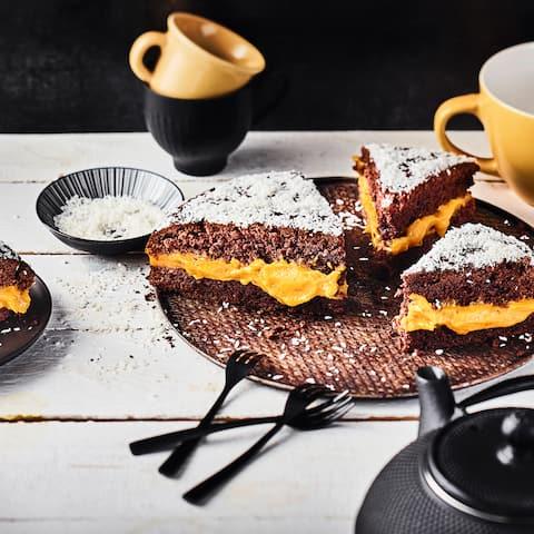 Cremiges Kürbispürree zwischen zwei schokoladigen Kuchenböden getoppt mit köstlichen Kokosraspeln - unser herbstlicher Kürbis-Schoko-Kuchen besticht mit jeder Menge Aromen.