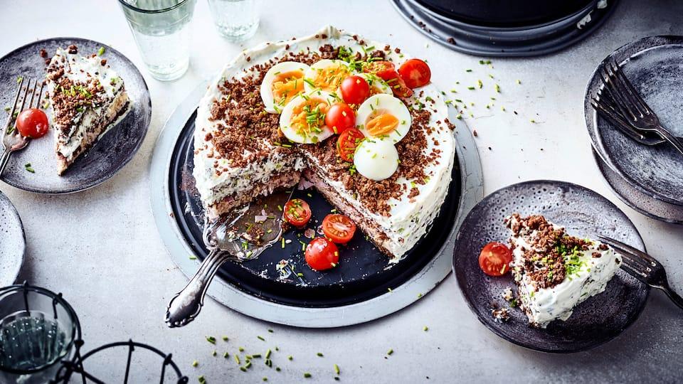 Bereiten Sie mithilfe einer Schinken-, einer Käsefüllung sowie nahhaftem Roggenvollkornbrot eine herzhafte Kuchenvariante zu: unsere Schwarzbrottorte.