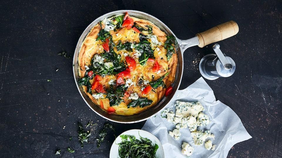 Spaghetti-Omelette mit Spinat und Blauschimmelkäse, belegt mit Tomaten und frittiertem Rucola. So wird aus einem einfachen Omelette ein kulinarischer Gaumenschmaus!