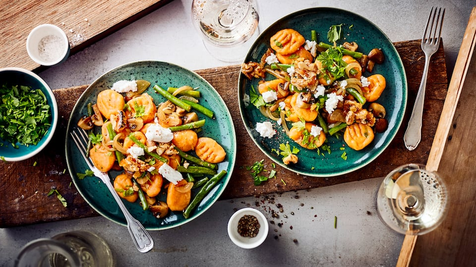 Italienischer Pasta-Klassiker mal anders! Unser Rezept für Süßkartoffel-Gnocchi besteht aus selbstgemachten Gnocchi und einer aromatischen Beilage mit Ziegenkäse, Walnüssen, Champignons und Bohnen.