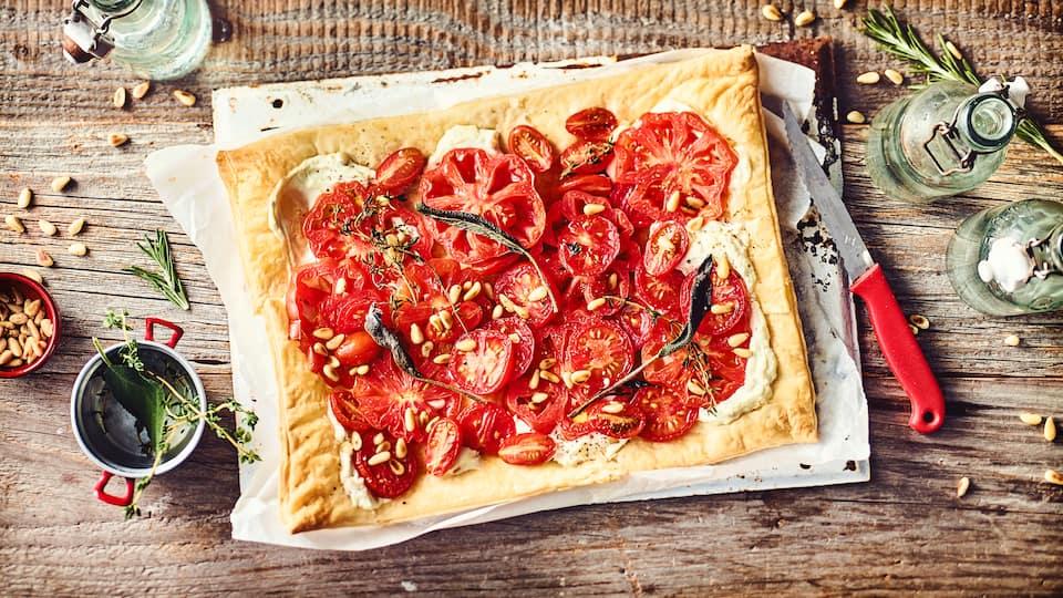 Leichtes Sommergericht vom Blech: Probieren Sie unsere Tomaten-Pinien-Tarte mit Ricotta und Zitronenthymian – vegetarisch und mediterran!