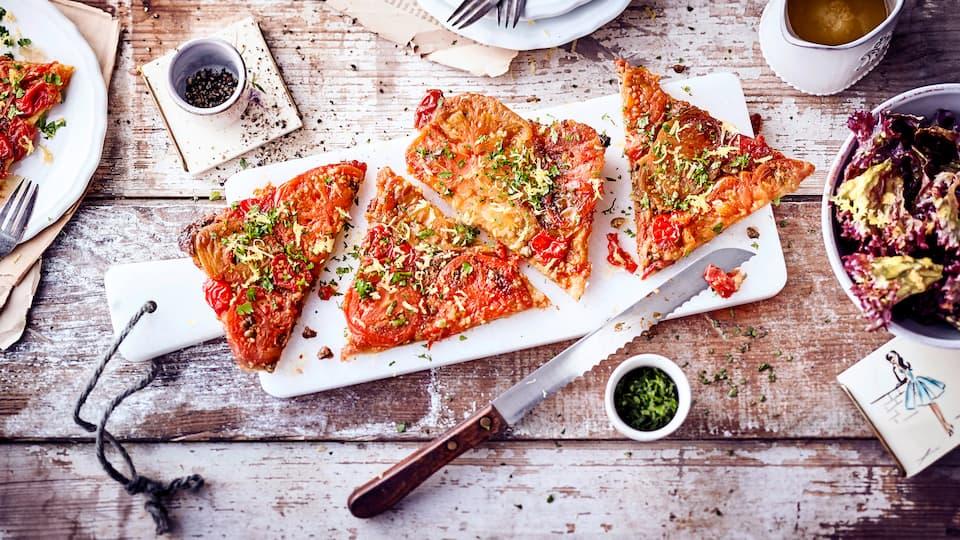 Verzaubern Sie Ihre Liebsten mit diesem pikanten Gemüsegericht aus dem Ofen: Probieren Sie unsere Kirschtomaten-Tarte-Tatin mit frischen Kräutern und einem selbstgemachten Ziegenfrischkäse-Dip.