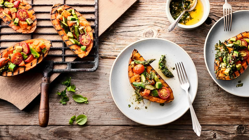 Eine fantastische Beilage, die Sie so vielleicht noch nicht probiert haben: Süßkartoffel vom Grill mit Tomaten-Avocado-Spargel-Topping und selbstgemachter Kräutersoße.