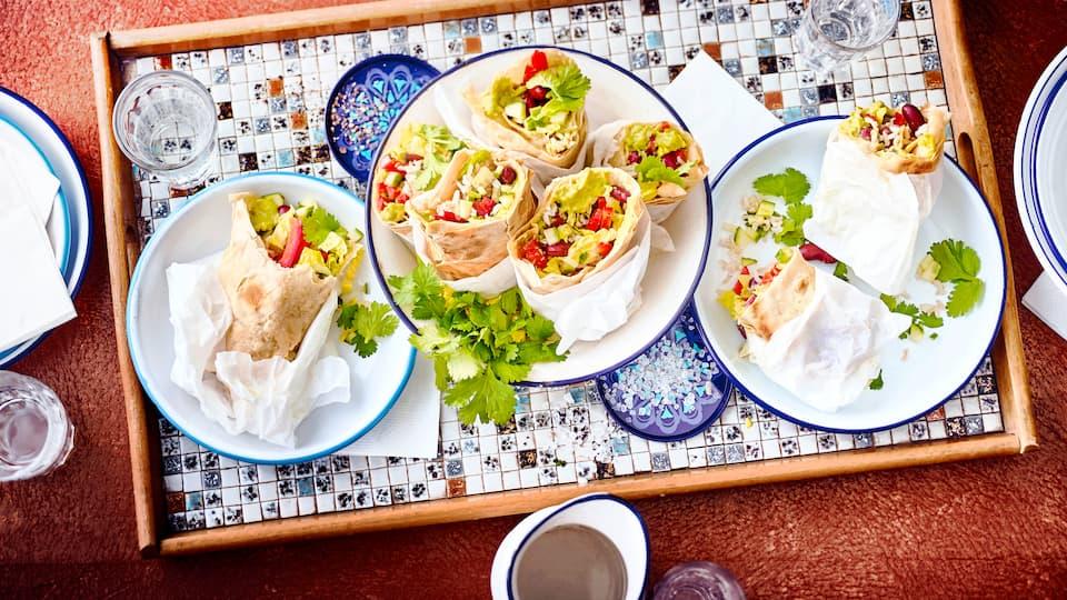 Selbst gemachte Tortillas, gefüllt mit frischem Gemüse, Guacamole, Bohnen und Reis. Ein besonderer Genuss. Probieren Sie unsere veganen mexikanischen Wraps.