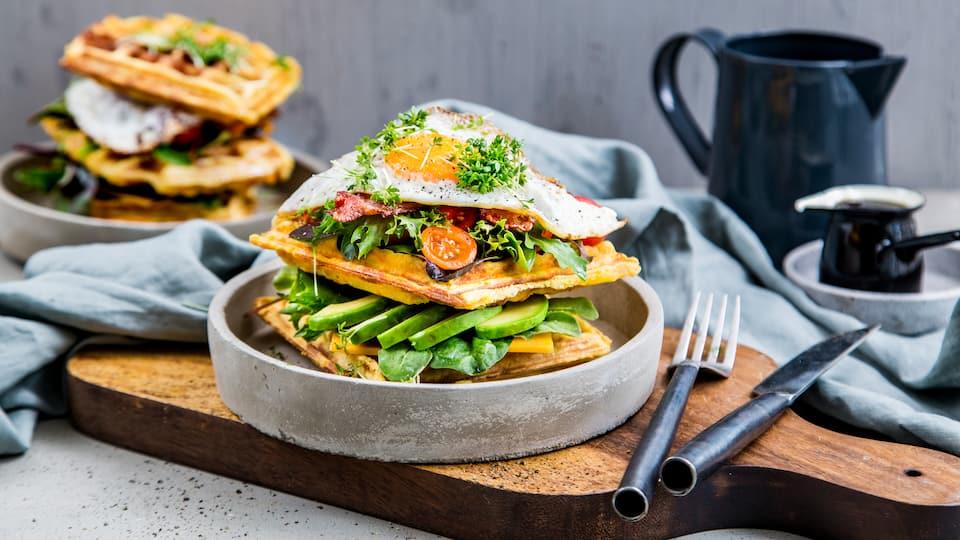 Kennen Sie schon Waffel-BLT? Sonst wird es höchste Zeit für die herzhafte Süßkartoffel-Polenta-Waffel mit Bacon, Eiern, Avocado und würzigem Cheddar.