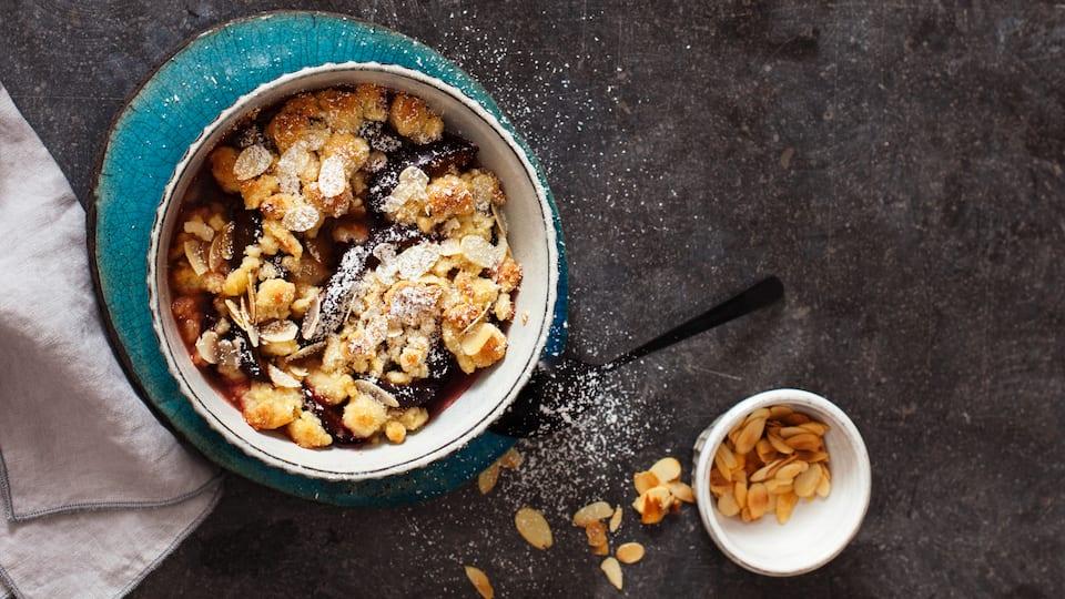 Probieren Sie unser Rezept für den Zwetschgen-Marzipan-Crumble mit gehobelten Mandeln und Lebkuchengewürz unbedingt aus – die perfekte Kombination!